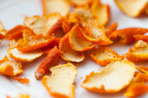 dried orange zests on white background