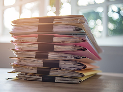 Stacked documents on the office desk.