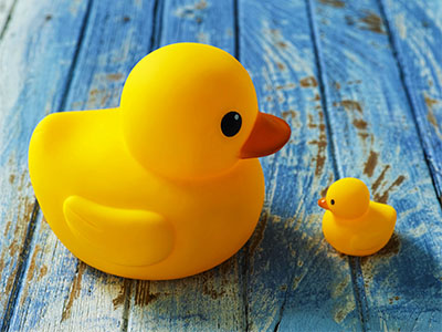 Two rubber ducks, one big and one small face each other as if talking together. Conceptual image realting to different points of view, intimidation, underdog, parent with child, advice. The ducks are sitting on an old weathered wooden background representing conceptual water.