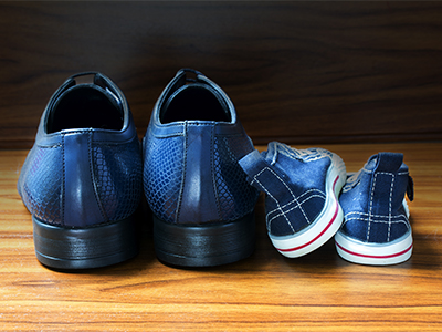 Men shoes and children sneakers from behind side by side on the wooden floor, concept of family, at home and father's day