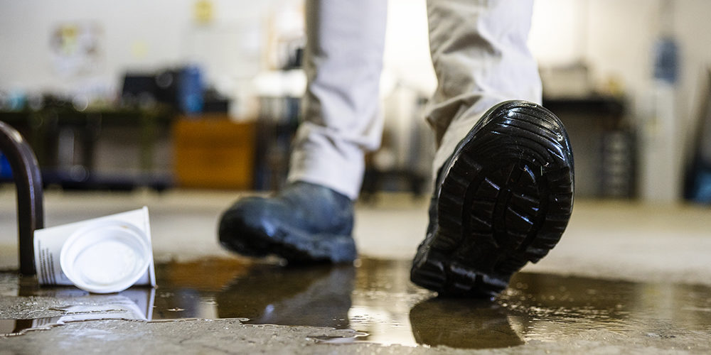 A male worker wearing work boots in a warehouse walking into a liquid spill on the floor.